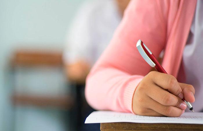 Primer plano estudiantes que escriben y leen las hojas de respuestas del examen ejercicios en el aula de la escuela